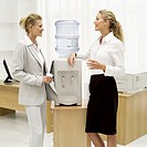 two businesswomen talking beside a water dispenser