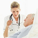 female nurse reading a thermometer sitting next to an old man