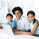 portrait of a father with his son and daughter in front of a laptop