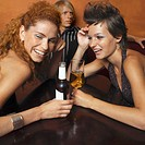 portrait of two young women sitting at a table in a bar with their drinks