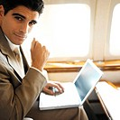 portrait of a businessman using laptop in an airplane