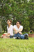 Couple in park, sitting on grass, looking away
