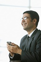 Businessman holding PDA, smiling, looking away