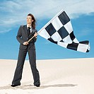 young woman holding the checkered flag in the desert