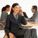 Businesswoman sitting in a wheelchair talking on mobile phone and business executives sitting around a table in the background