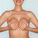 mid section of a nude woman covering her breasts