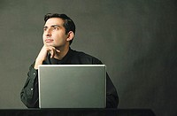 Man with hand on chin, laptop open in front of him