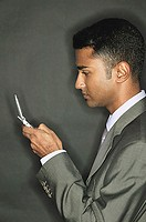 Businessman using mobile phone, side view
