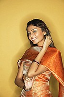 Woman in Indian clothing, smiling at camera, hand on neck