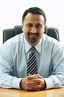Businessman sitting, smiling at camera, portrait