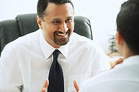 Businessman smiling at person in front of him