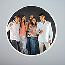 portrait of a group of people holding champagne glasses seen through a circle