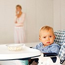 Baby boy (12-18 months) sitting in high chair in foreground with mother in the background (blurred)
