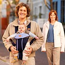 Front view portrait of father taking baby son (6-12 months) for a walk in a baby sling with mother standing in the background