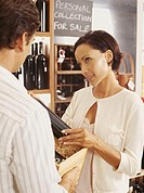mid adult man selling wine to a young woman