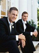 groom and his best man sitting on the steps