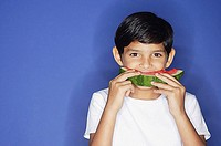 Boy looking at camera, eating watermelon