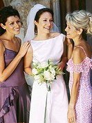 bride standing outside a church with her mother and bridesmaid