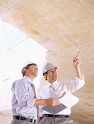 low angle view of two architects looking up at a construction site