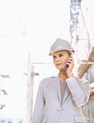 close-up of a female architect holding a mobile phone at a construction site