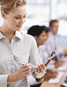 close-up of a businesswoman holding a clipboard and a pen