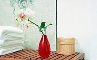 Orchid in a vase on a wooden table with towels