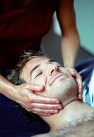 Physical therapist is giving a facial massage to a young man