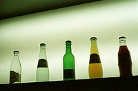 Group of bottles with table water or soda or soft drinks on a board, light in the background (thumbnail)