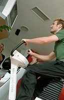 Young man at the fitness studio, gym, working out, doing exercises, cycling