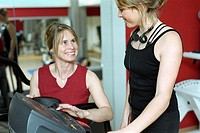 Young woman at the gym, fitness center, walking on the treadmill, instructed by a coach