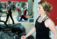 Young woman at the gym, fitness center, walking on the treadmill (thumbnail)