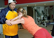 Young woman at the gym, fitness center, doing exercises at an athletic implement, instructed by a coach, trainer