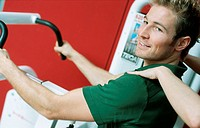Young man at the fitness studio, gym, working out, doing exercises at an athletic implement, instructed by a coach, trainer