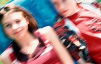 A boy and a girl, a young couple or friends, are sitting on a blue inflatable deckchair in the garden, unsharp, blurred