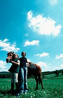 Two girls standing in the open countryside with a horse