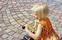 A little girl, 5-10 years old, playing in the garden, driving a three wheeler