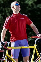 A young man 15-20 20-25 25-30 years old, sportsman, biker, cyclist, with his bike, outside in summer (thumbnail)