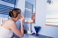 A young woman, 20-25 25-30 years old, in the bathroom, removing the make-up in front of a mirror