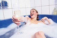 A young woman, 20-25 25-30 years old, in the bathroom, having a foam bath, bathing