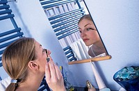A young woman, 20-25 25-30 years old, in the bathroom, putting mascara on her eyelashes in front of a mirror