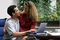 A young man and a young woman, couple, 25-30 30-35 35-40 years old, sitting on a balcony or terrace at a table with a laptop
