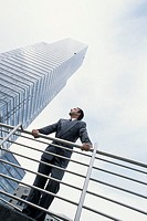 A young man, businessman, 25-30 30-35 35-40 years old, in front of a modern office tower, office building