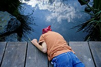 A boy, 5-10 years old, lying on a footbridge, looking into the water of a pond outside in the garden in summer