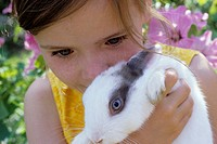 Portrait of a girl, 5-10 years old, in the garden in summer, holding a rabbit, bunny in it´s arms