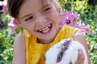 Portrait of a girl, 5-10 years old, in the garden in summer, holding a rabbit, bunny in it's arms