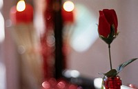 A red rose out of fabric and a burning candle in the background