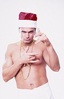 A young man, 20-25 25-30 30-35 years old, stripped to the waist, wearing a Santa Claus cap, white shorts and a golden necklage