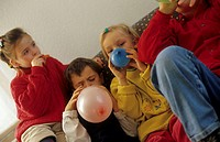 Four children, boys and girls, 5-10 years old, sitting on a sofa, inflating balloons