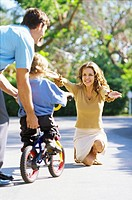 mid adult couple helping their child ride a bicycle