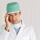 male surgeon wearing scrubs standing with his hand on his head